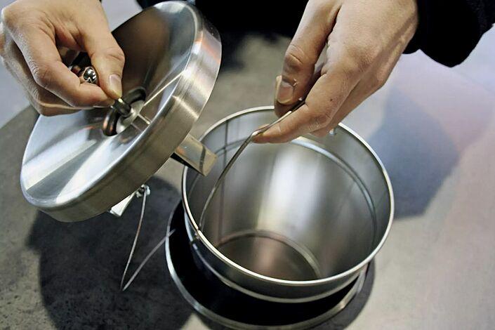 Deckel (mit Sicherungsdraht) entnehmen und Innenbehälter mittels Henkel entfernen