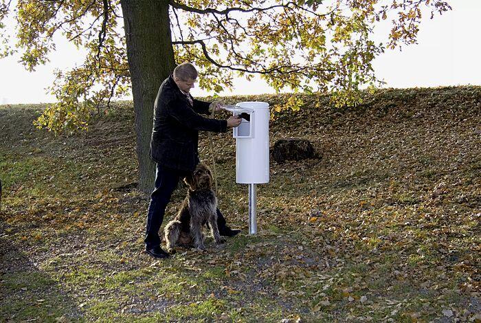 Beutel entnehmen, Hundekot mit umgestülptem Beutel aufnehmen und zuknoten