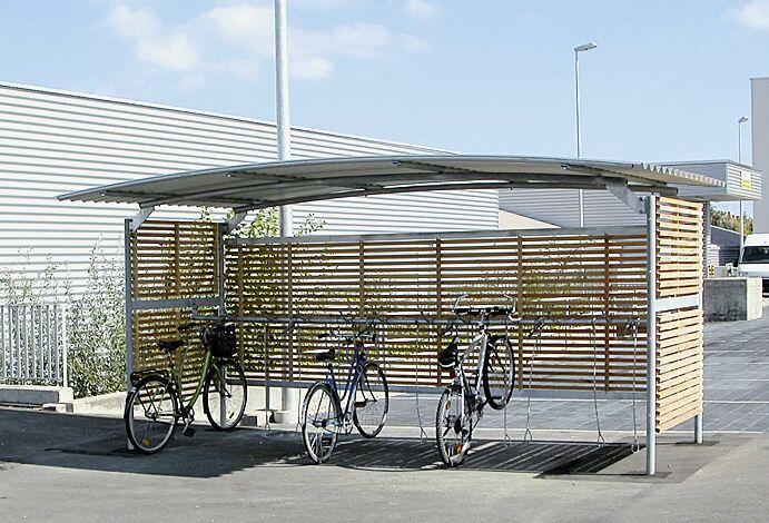 Fahrradüberdachung BWA bausystem®, einseitig, Dach Stahlwellblech, Rück- und Seitenwände mit Holzlamellen, ausgestattet mit Lenkerhaltesystem ARKANSAS