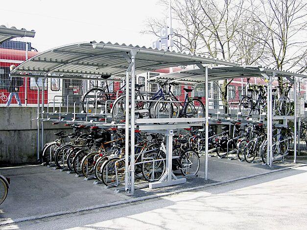 Fahrradüberdachung BWA bausystem® mit Fahrradparker (auf Anfrage)<br> Für beengte Platzverhältnisse ist die erhöhte Fahrradüberdachung mit dem Doppelstockfahrradparker eine kluge Lösung.<br> Lichte Höhe ca. 2700 mm. Bei der doppelseitigen Überdachung können bis zu 40, bei der einseitigen bis zu 20 Einstellungen untergebracht werden. Fahrradparker mit Radabstand 500 mm.