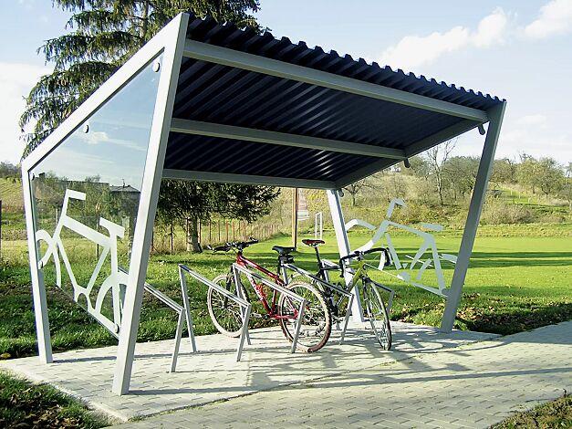 Fahrradüberdachung EDGE, einseitig, mit Dacheindeckung Trapezblech, auftragsbezogenes Scheibendekor in der Seitenscheibe, mit Anlehnbügel EDGETYRE, Stahlkonstruktion in RAL 9006 weißaluminium<br /> <br /> Fahrradüberdachung EDGE Dachbreite x Dachtiefe 3900 mm x 2500 mm und Anlehnbügel EDGETYRE, Stahlkonstruktion spritzverzinkt und pulverbeschichtet inkl. Seitenwänden ESG, Klarglas, Dacheindeckung Trapezblech bandverzinkt<br /><br />Fahrradüberdachung EDGE mit Anlehnbügel EDGETYRE Dachbreite x Dachtiefe 3900 mm x 2500 mm, Stahlkonstruktion spritzverzinkt und pulverbeschichtet inkl. Seitenwänden ESG, Klarglas, Dacheindeckung Trapezblech bandverzinkt