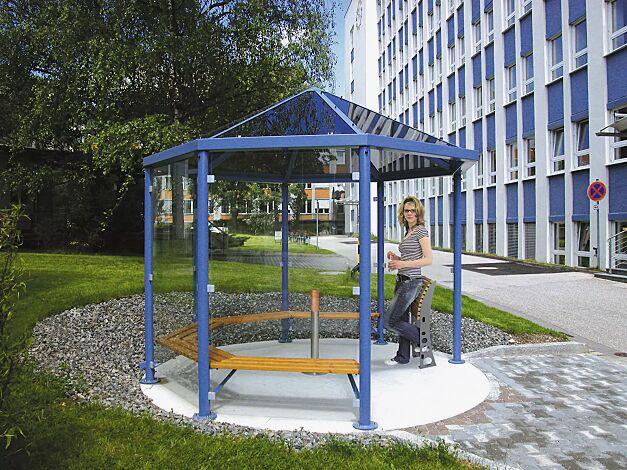 Einzel-Pavillon AQUA, mit 5 Holzsitzbänken, Anlehnstütze RELIEF und Ascher CYCAS, Dacheindeckung VSG bronce getönt (auftragsbezogene Anpassung), 6 Seitenwandscheiben ESG Klarglas, Stahlkonstruktion in RAL 5015 himmelblau