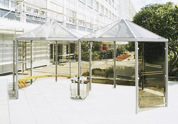 Zweier-Pavillon AQUA mit umlaufenden Holzsitzbänken, 10 Seitenwandscheiben ESG bronce getönt (auftragsbezogene Anpassung), mit Siebdruckstreifen, Dacheindeckung VSG Klarglas, Stahlkonstruktion in DB 703 eisenglimmer