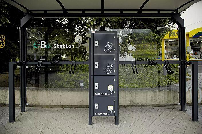 Schließfachanlage SECURE, je 2 Fächer mit / ohne Elektroinstallation, Beschriftung bauseits, integriert in Fahrradüberdachung MATRIX mit Design-Lenkerhaltesystem UNIT, Stahlkonstruktion in RAL 7016 anthrazitgrau