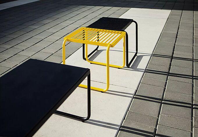 Sitz STACK ohne Rückenlehne, in RAL 1021 rapsgelb und RAL 9005 tiefschwarz sowie Tisch STACK mit HPL-Auflage in schwarz, Stahlteile in RAL 9005 tiefschwarz