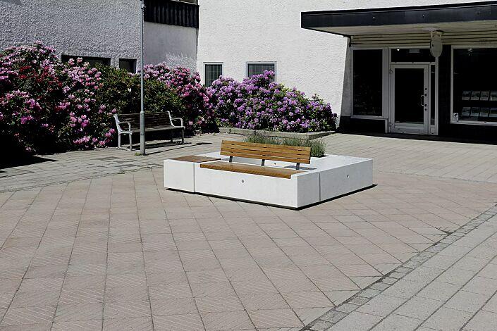 Sitzbänke DEMETRA mit und ohne Rückenlehne, aus Beton, teilweise mit Okouméholzbelattung, in Granitoptik weiß sowie Pflanzbehälter KUBB