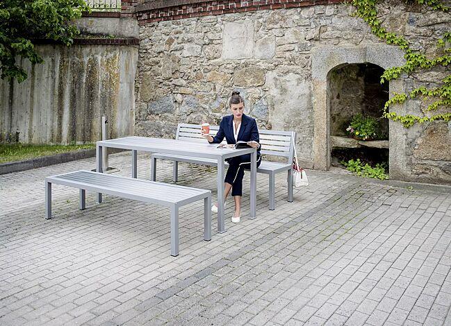 Sitzbank LIGURIA mit und ohne Rückenlehne, zum freien Aufstellen, mit Edelstahlauflage, Stahlgestell in RAL 9007 graualuminium sowie Tisch LIGURIA und Ascher FINTWIN