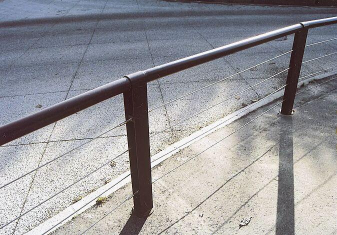 Systemgeländer CYDLIMIT bestehend aus Mittelpoller mit Edelstahldrähten und Verbindungsrohren, in RAL 7022 umbragrau