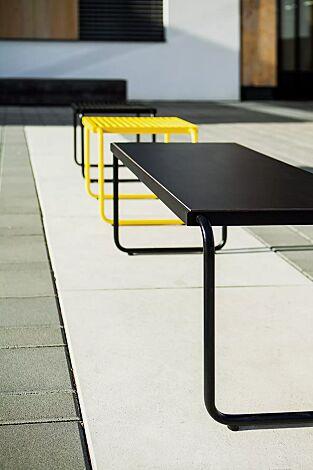"""<div id=""""container"""" class=""""container"""">Tisch STACK mit HPL-Auflage in schwarz sowie Sitz STACK ohne Rückenlehne, Stahlteile in RAL 1021 rapsgelb und RAL 9005 tiefschwarz</div>"""