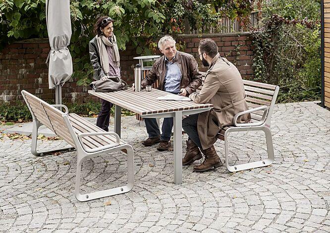 Tisch UNI ONE mit Jatobaholzbelattung, Stahlteile in RAL 9006 weißaluminium und Sitzbank PORTIQOA sowie Abfallbehälter DIAGONAL