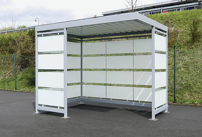 Wartehalle AQUILA mit auftragsbezogener Anpassung, Dachbreite x Dachtiefe 3180 mm x 2165 mm, Rück- und Seitenwände sowie zusätzliche Windschutzwand mit Siebdruckstreifen, Stahlkonstruktion in RAL 9006 weißaluminium