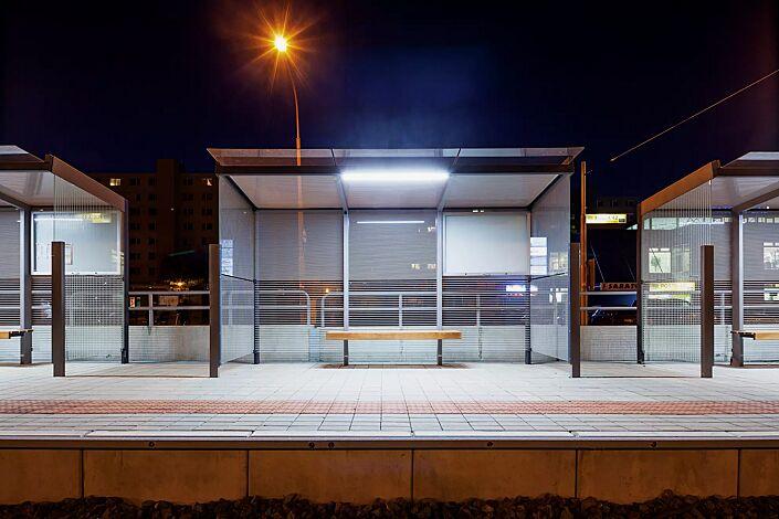 Wartehalle GEOMERE, Dachbreite x Dachtiefe 4180 mm x 1700 mm, Rück- und Seitenwände mit auftragsbezogenem Scheibendekor und Schaukasten, Sitzbank mittig, Stahlkonstruktion in RAL 7016 anthrazitgrau