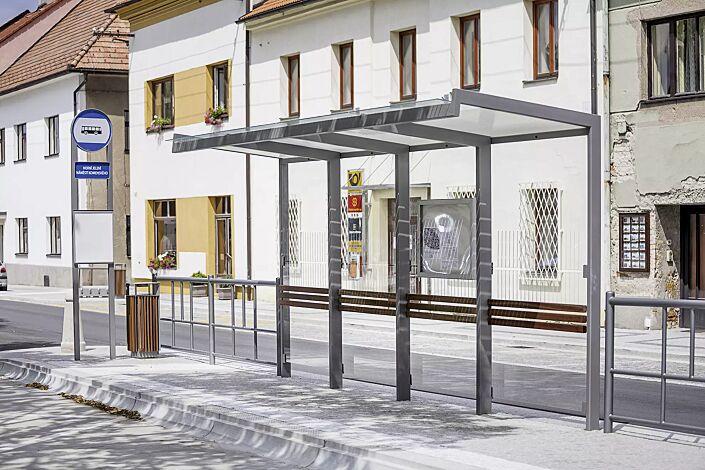 Wartehalle GEOMERE, Dachbreite x Dachtiefe 5540 mm x 1700 mm, Rückwand ESG, Klarglas, auftragsbezogene Ausführung mit Anlehnbügel aus Holz, Stahlkonstruktion in RAL 9006 weißaluminium