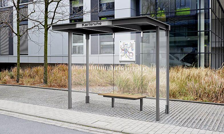 """<div id=""""""""container"""""""" class=""""""""container"""""""">Wartehalle HOREC, Dachbreite x Dachtiefe 2955 mm x 1484 mm, mit Rück- und Seitenwänden Verbundsicherheitsglas (VSG), mit Sichtstreifen, Sitzbank mittig, Fahrplanschaukasten und LED-Beleuchtung, Stahlkonstruktion in RAL 9007 graualuminium</div>"""